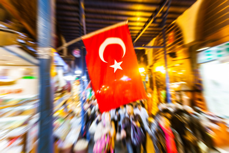 obtain: Turkish flag at Istanbul main market. Photo taken with zoom-in technique to obtain the blur effect on camera. Blurred people walking on background