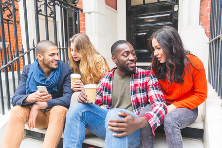 residential houses: Multiracial group of friends having fun together in London. Two girls and two boys, talking and laughing. Residential district with houses and cars on background. Lifestyle and friendship concepts. Stock Photo