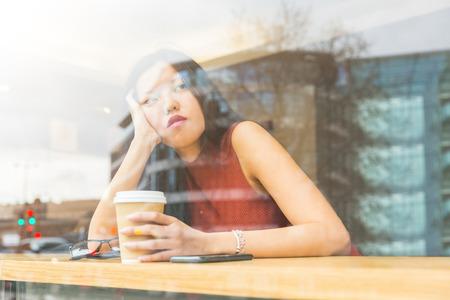 niñas bonitas: Mujer china triste en un café en Londres. Ella está sentada sola en una mesa frente a la ventana, mirando hacia fuera y sosteniendo su cabeza con una mano. La tristeza y la soledad conceptos. Foto de archivo
