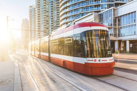 Modern tram in Toronto downtown at sunset. There is no traffic in the road, and nobody on the platform. Travel and transportation concepts. 免版税图像