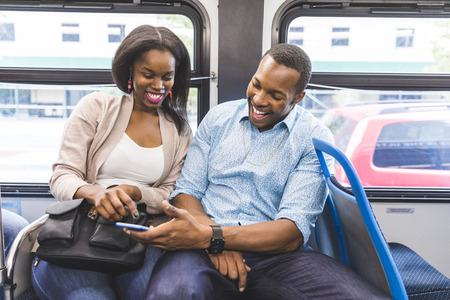 happy couple: Happy black couple travelling by bus in Chicago. A man and a woman sitting in the bus and looking at the smartphone. They are laughing and enjoying time together. Lifestyle and happiness concepts.