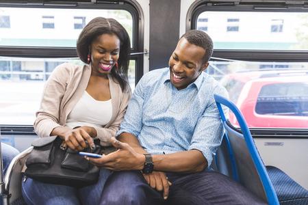Gelukkig zwart stel reizen per bus in Chicago. Een man en een vrouw zitten in de bus en kijken naar de smartphone. Ze lachen en genieten van tijd samen. Levensstijl en gelukconcepten.