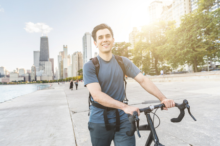 Man walking carrying his bike in Chicago. Young caucasian man looking at the camera, smiling. Downtown skyscrapers on background. Urban outfit, travel and youth culture concepts.
