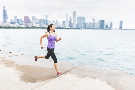 Young woman jogging in Chicago with skyline on background. Panning technique, focus on the face with blurred background. Fitness and lifestyle concepts