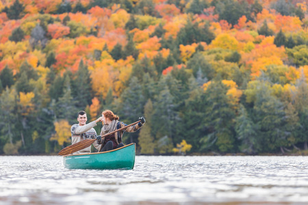Happy couple canoeing in a lake in Canada. There are many trees on background with colourful leaves during autumn. They are young and happy, enjoying a canoe trip together. Wanderlust and nature concepts.