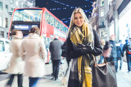 early twenties: Beautiful woman portrait in London on Christmas time. Blonde woman, on her early twenties, wearing warm clothes and looking at camera. Christmas lights on background. Cold colours applied for the mood