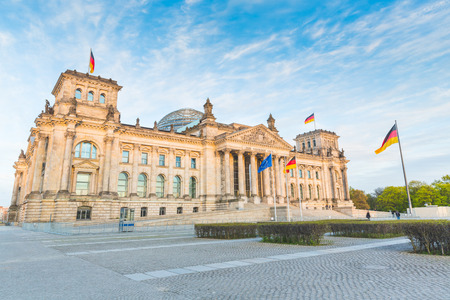 parliament building: German Reichstag, the German parliament building in Berlin at sunset. Some german flags and one European waving. Politics and architecture concepts. Stock Photo