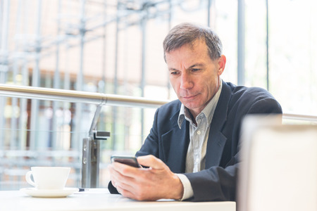 Businessman looking at the smart phone in a cafe. Caucasian man on his late fifties, typing on his smart phone. There is a coffee on the table. Business and lifestyle concepts.
