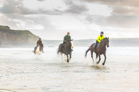 Horses galloping on the beach. Three people riding horses at seaside on a stormy day. Epic photo of horses on the sea with water splashing. Sport and travel concepts