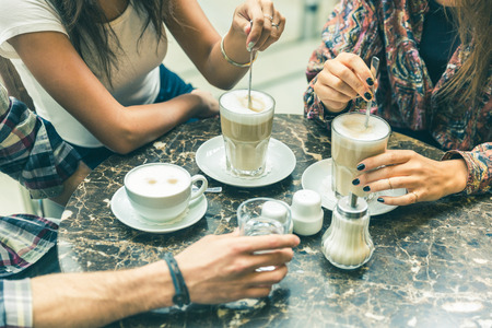 Multiracial group of friends at cafe together. Two women and a man at cafe, focus on glasses and cups, with coffee and cappuccino. Friendship and coffee culture concepts with real people models.