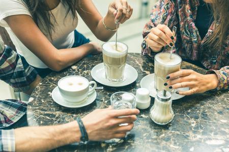 Multiraciale groep vrienden bij cafe samen. Twee vrouwen en een man in cafe, focus op glazen en kopjes, met koffie en cappuccino. Vriendschap en koffiecultuur concepten met echte mensen modellen. Stockfoto