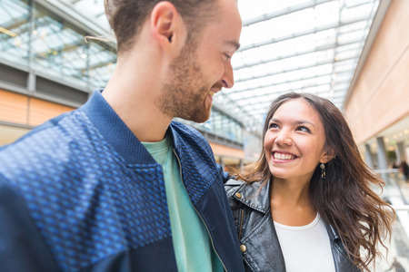 friendship: Happy multiracial couple walking in the city. Young man and woman looking each other and smiling. Happy people or best friends enjoying time together. Love and friendship concepts Stock Photo