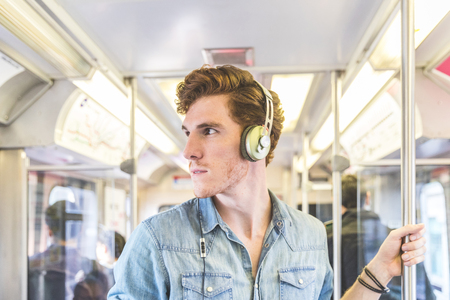 Young man on the train in Chicago. Portrait of a ginger young man listening music with headphone while travelling in the city.