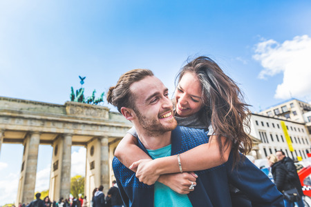 Happy couple having fun in Berlin. Mixed race couple, a caucasian man giving a piggyback ride to his girlfriend, an asian woman. Happiness, lifestyle and tourism concepts