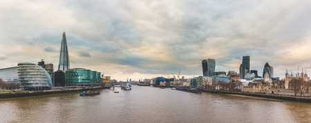 Panoramic view of London from Tower Bridge on a cloudy day. Famous buildings and skyscrapers of the city are easily recognisable on both sides of Thames river