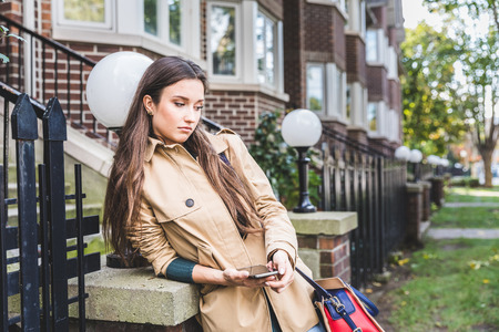 residential houses: Sad woman with a smart phone in a residential area. Bored young woman waiting for someone, outdoors, with houses on background. Failure and sadness concepts. Stock Photo