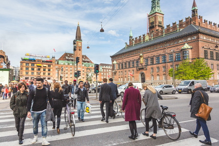 COPENHAGEN, DENMARK - APRIL 27, 2015: People crossing on zebra in the city. Commuters and tourists walking and carrying bicycles. City hall on background Editorial