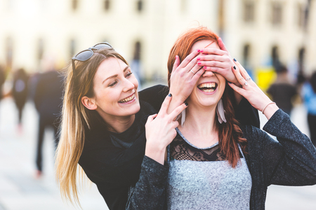covering: Two young women having fun together. Blonde girl playing peekaboo with her redhead friend. Happiness and lifestyle concepts, candid real people as models
