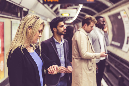 Group of people on the platform at train station in London. They are a mixed group of persons, wearing smart casual clothes. Friends or just strangers. Urban lifestyle and transportation concepts. photo