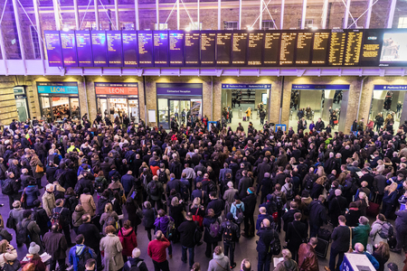 railway transportations: LONDON, UK - FEBRUARY 23, 2017: Crowded Kings Cross station in the city. Hundreds people waiting for the train, with delays and cancellations as Storm Doris lashes UK