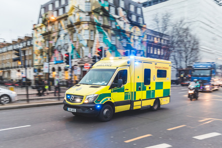 LONDON, UK - MARCH 1, 2017: Emergency ambulance rushing on the street with emergency lights flashing in London city centre Stock Photo - 73155835