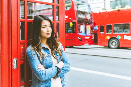 young lady: Portrait of a beautiful young woman in London. Asian woman leaning to a red phone booth with red double decker bus on background. Travel and tourism concepts