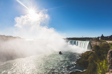 Niagara Falls panoramic view. Backlight view of the beautiful horse shoe fall at Niagara, from the Canadian side with tourist boat. Very famous and majestic destination Stock Photo