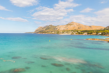 Crystal clear water at seaside in Mallorca, long exposure with clouds on the sky and mountains on background. Summer, tourism and travel concepts. Stock Photo - 78390408