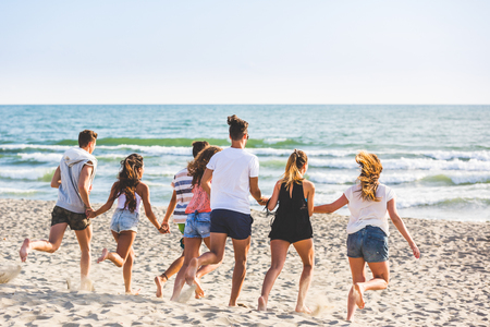 Multiracial group of friends running on the beach. Four girls and three boys, wearing trunks and colourful t-shirts, having fun at seaside. Friendship and lifestyle concepts. photo