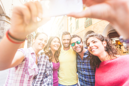 Group of friends taking a selfie in the city. They are young and happy, and they could be tourists or students. Summer related photo with concepts of friendhsip and lifestyle photo