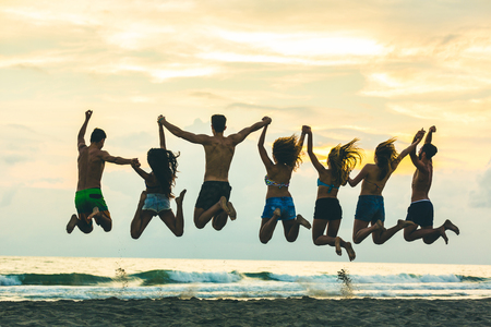 Silhouette of friends jumping on the beach. Four girls and three boys, wearing swimsuits and holding hands, having fun together at sunset. Happiness and success concepts in this colorful image. photo