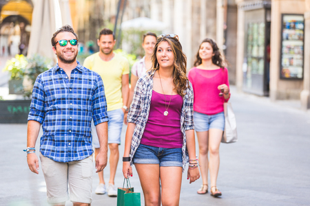 Friends walking in the city. They are young and happy, and they could be tourists or students. The photo was taken in Pisa, Italy, but could also be used for Rome, Florence or Milan.