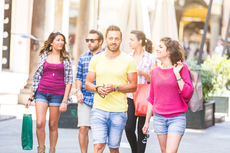 Friends walking in the city. They are young and happy, and they could be tourists or students. The photo was taken in Pisa, Italy, but could also be used for Rome, Florence or Milan. photo