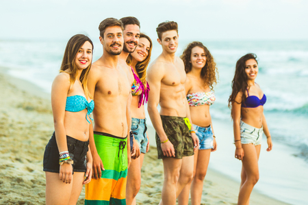 Multiracial group of friends on the beach. Portrait of four girls and three boys, wearing swimsuits and looking at camera. Color filter applied photo