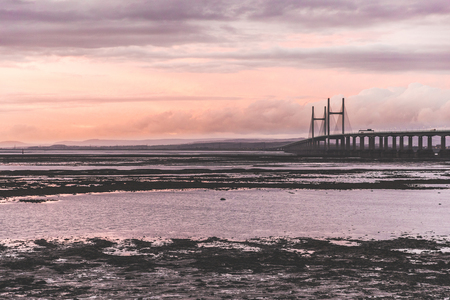 Second Severn crossing, a bridge linking Bristol to Wales. Panoramic view at sunset with low tide on the river. Travel and nature concepts Stock Photo