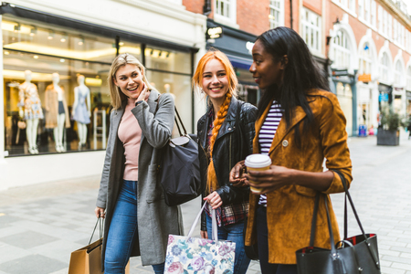 Girls shopping and walking in London. Three girls, multiracial group, having fun in the city while shopping. Best friends sharing happiness, lifestyle and friendship concepts photo