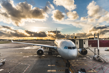 Airplane boarding passengers at airport at sunset. Long haul flight aircraft ready to leave from gate. Dramatic sky with clouds at sunset. Travel and transportation concepts