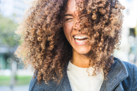 laughing out loud: Curly woman laughing and shaking head. Smiling mixed race woman with curls having fun. Smart casual dress. Lifestyle and hairstyle concepts Stock Photo