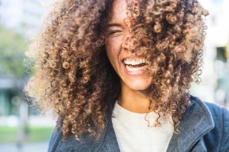 Une femme bouclée riant et tremblante. Sourire femme de race mélangée avec des boucles qui s'amusent. Robe décontractée élégante. Les concepts de style de vie et de coiffure