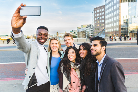 Group of business people taking a selfie in London. Mixed race group of people with Tower Bridge on background. Travel and lifestyle concepts. photo