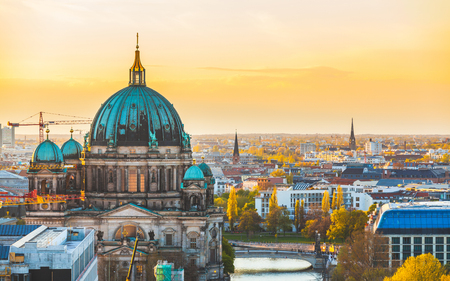 Berlin aerial view at sunset. Berlin Cathedral dome and cityscape. Golden light over Berlin rooftops in the late afternoon. Travel and architecture concepts