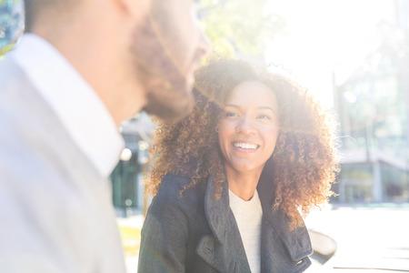 ビジネスの女性と話している男性。ビジネス人々 の休憩時間に会議、チャット、笑って。混合都市で美しいカップルを屋外レースします。ビジネス