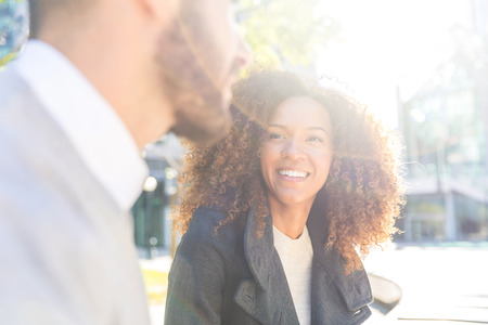 비즈니스 여자와 남자 이야기입니다. 비즈니스 사람들이 회의 휴식 및 채팅 웃고. 야외에서 도시에서 혼합 된 경주 아름 다운 커플입니다. 비즈니스 및