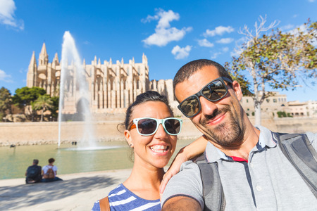 Tourists taking a selfie in Palma de Majorca with Cathedral on background. Young couple taking a self portrait on a sunny day in Spain. Travel and lifestyle concepts