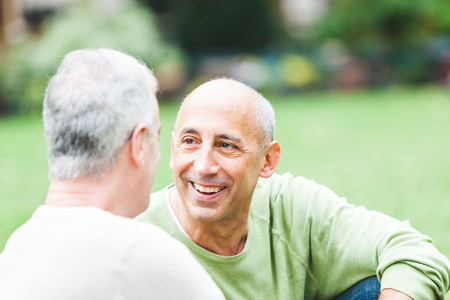Gay couple at park in New York. Two senior men relaxing together in New York city. Homosexual senior couple concept