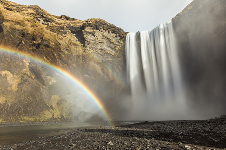Skogafoss waterfall and rainbow in Iceland. Beautiful view of skogafoss with a colourful rainbow on the left. Long exposure image. Nature and travel concepts Stock Photo