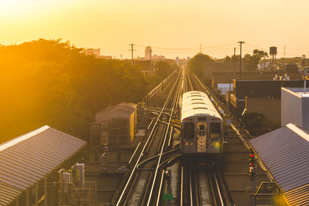 Subway train at sunset in Chicago. Panoramic view of elevated tracks and station at sunset with train leaving. Travel and transportation concepts. Banco de Imagens