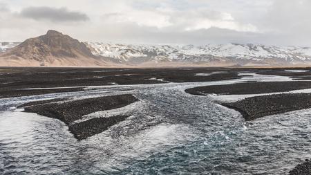 岩河床とアイスランドの背景の山にストリーム。川と山とアイスランドの自然と野生の風景のパノラマ風景。旅行と自然の概念