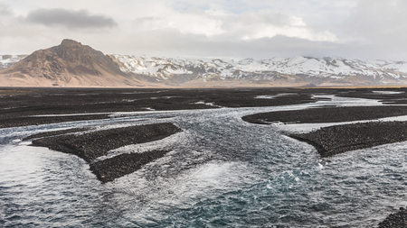 alluvial: Rocky riverbed and stream with mountains on background in Iceland. Panoramic view of natural and wild landscape in Iceland with river and mountains. Travel and nature concepts