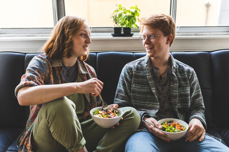 healty: Couple eating healty salad at home on the sofa. Man and woman relaxing and having a healthy meal. Salad, tomatoes, sweetcorn and radicchio. Healthy eating and lifestyle concepts